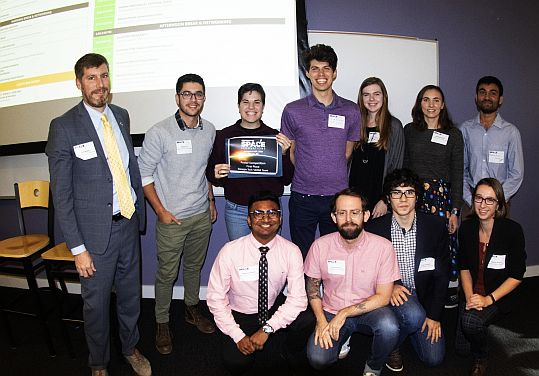 """Best Poster. All four of the teams that presented research under the theme """"Vertical Entry Robot for Navigating Europa (VERNE)"""" received the top award for their work. They are seen here with Dr. Jud Ready."""